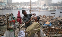A man has his beard groomed at a street salon on the bank of the Buriganga river in Dhaka, Bangladesh.