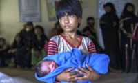 Rohingya Muslim girl Afeefa Bebi, who recently crossed over from Myanmar into Bangladesh, holds her few-hours-old brother.