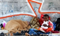 A child sits on the street as his mother sleeps, next to the Tiburtina station in Rome, Italy.