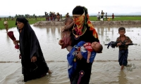 A Rohingya refugee woman carries children while walking in the water after travelling over the Bangladesh-Myanmar border in Teknaf, Bangladesh