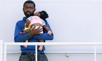 A migrant holds a baby as he waits to disembark from Italian Navy ship Sirio in the Sicilian harbour of Augusta, Italy.