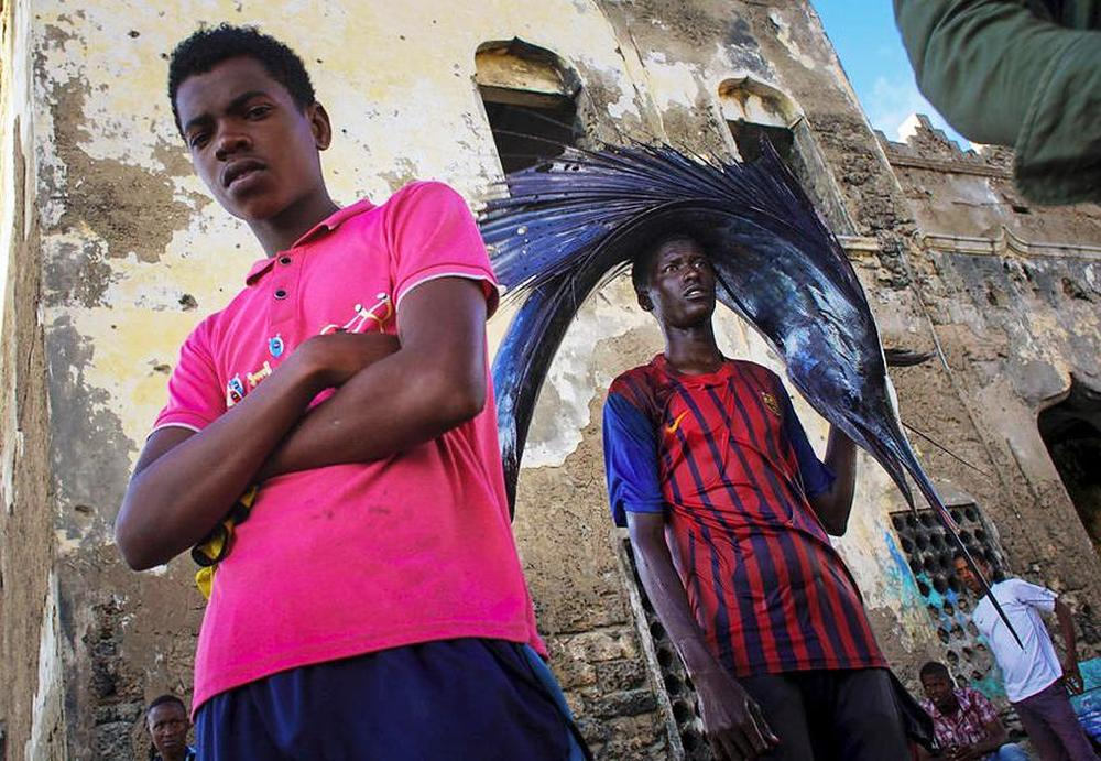 Somali boy with a freshly caught sailfish on his way to the market.