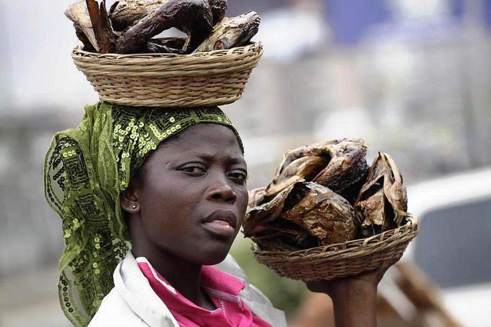 Nigerian girl selling dried fish at the market in Lagos.