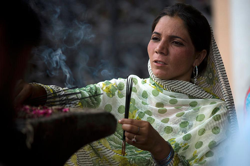 A Pakistani woman lights incense sticks at a local shrine in suburbs of Islamabad.