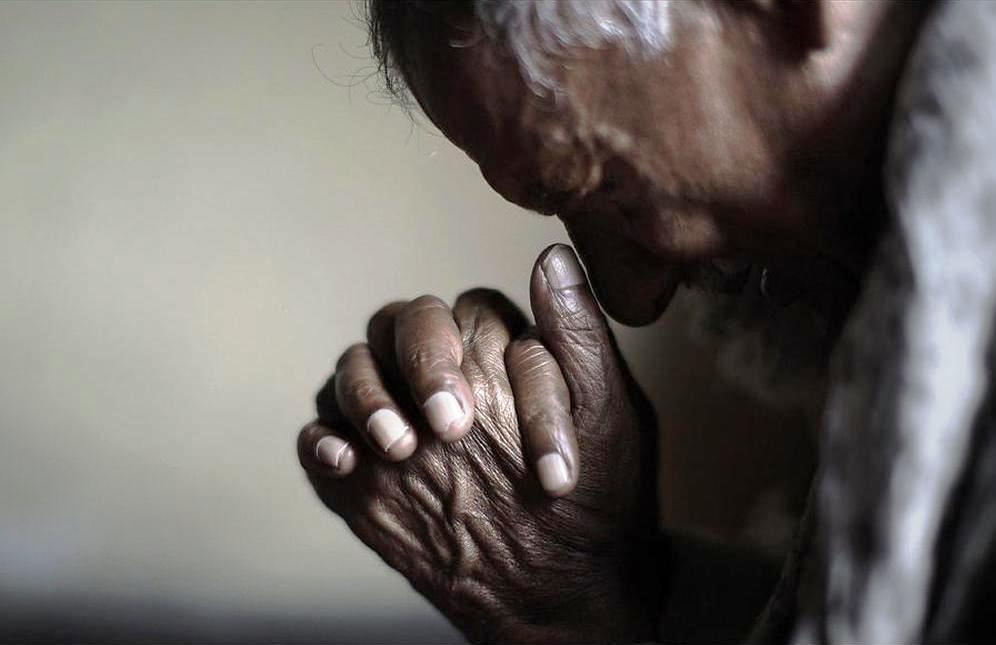 An elderly Pakistani Christian man prays during a Mass on Good Friday in a church in Islamabad.