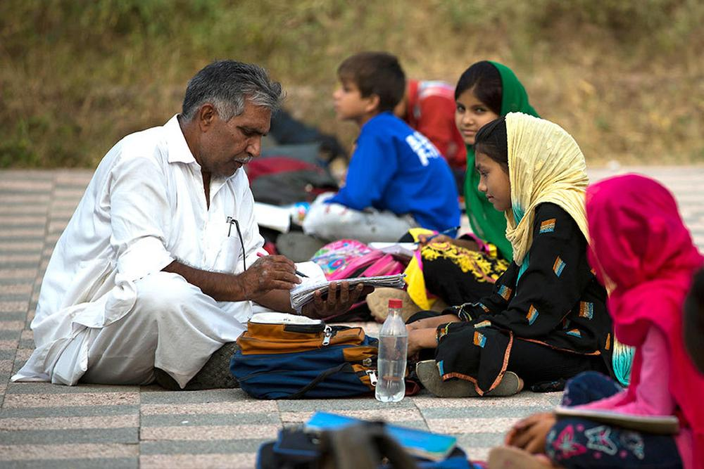 A government teacher with poor children from slums at a makeshift school in a park in Islamabad.