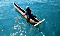 Young fisherman and primitive wooden fishing boat