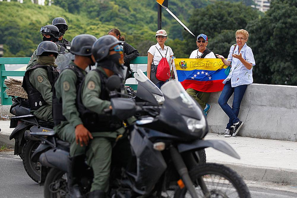 """Opposition supporters hold a national flag with the word """"Resistance"""" written on it as they face members of the National Guard, in Caracas, Venezuela."""