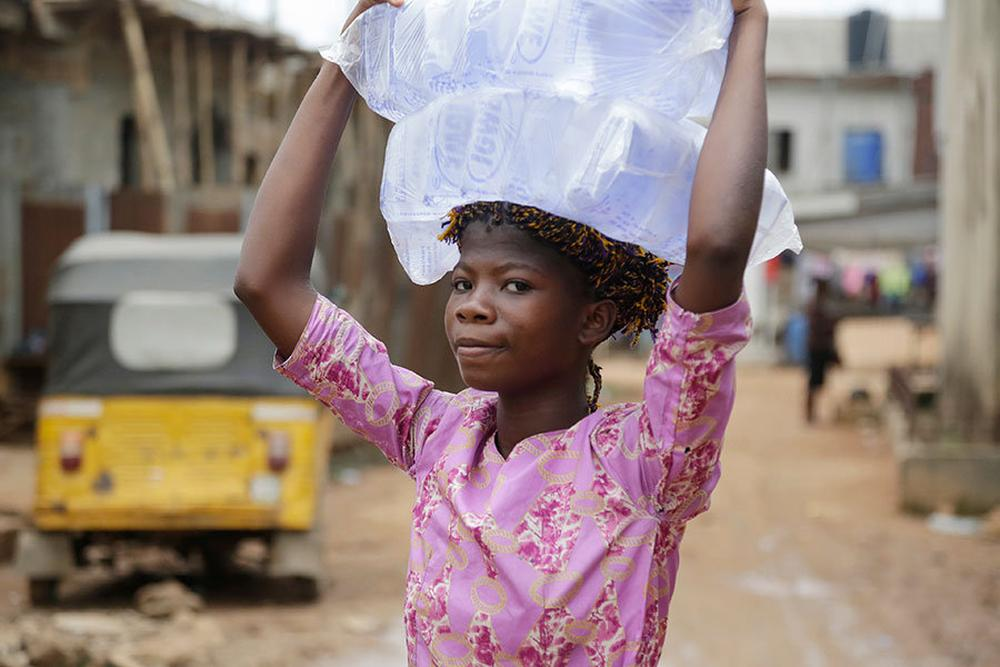 A girl carries bags of sachet water she bought in Baruwa Lagos, Nigeria.