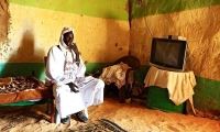 A Sudanese man from the Bedouin ethnic group sits inside his house in Malha, a town in Sudan's North Darfur.