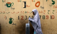 Nigeria. A girl draws water from a fountain in Kano.