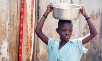 Uganda. A girl carries a pot of water on her head.