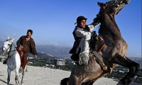 Afghans ride their horses on a hill overlooking Kabul.