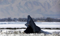 A woman walks along a snow-covered street on the outskirts of Kabul.