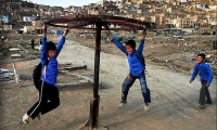 Children enjoy a ride on a makeshift merry-go-around next to a cemetery in Kabul.
