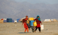 Refugee girls carry drinking water in containers at a refugee camp on the outskirts of Jalalabad.