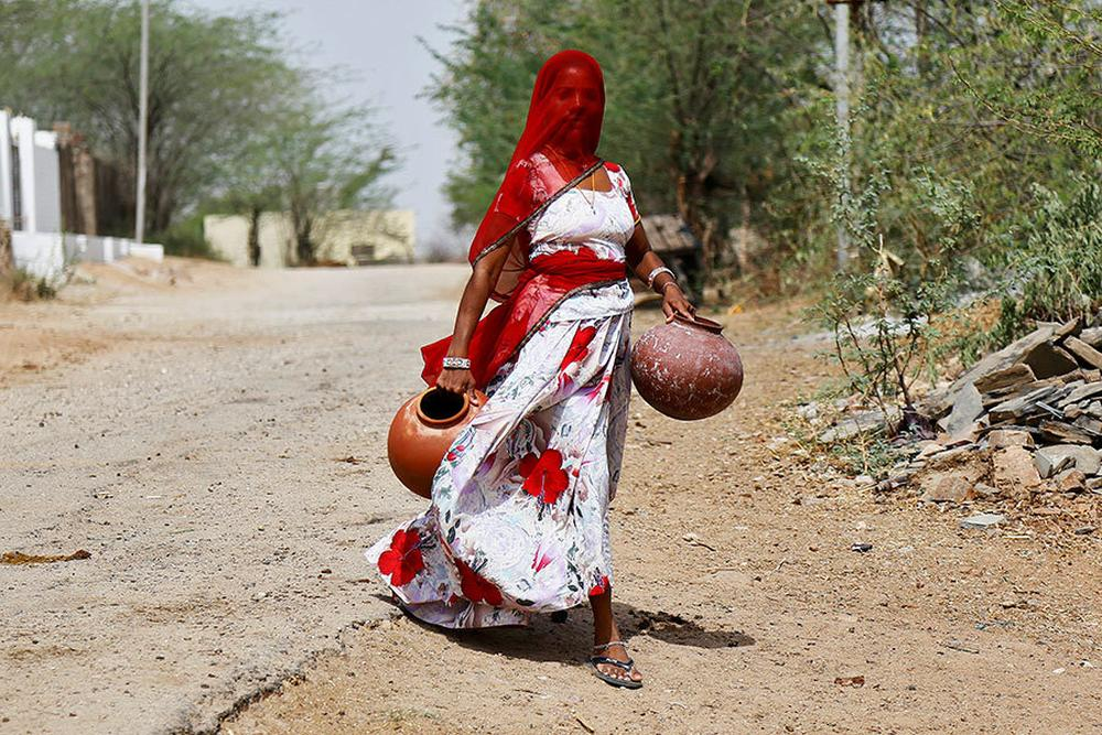 India. A woman carries earthen pots to fill them with drinking water on a hot summer day, on the outskirts of Ajmer, Rajasthan.
