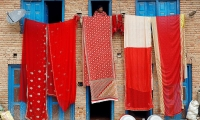 Nepal. A women looks out of a house window as saris are hanged out to dry in Lalipur.