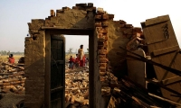 Nepal. Villagers stand on debris left after a storm hit in Bara district.