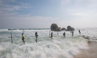 Sri Lanka. Fishermen climb higher on their poles after waves hit the shore in Weligama.