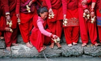 A Nepalese Hindu devotee washes her feet as she waits to collect holy water from Bagmati River.