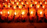 Nepal. Monks with lit candles attend an event to spread the message of 'world peace'.