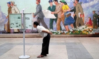 North Korea. A man reads newspapers at a subway station in Pyongyang.