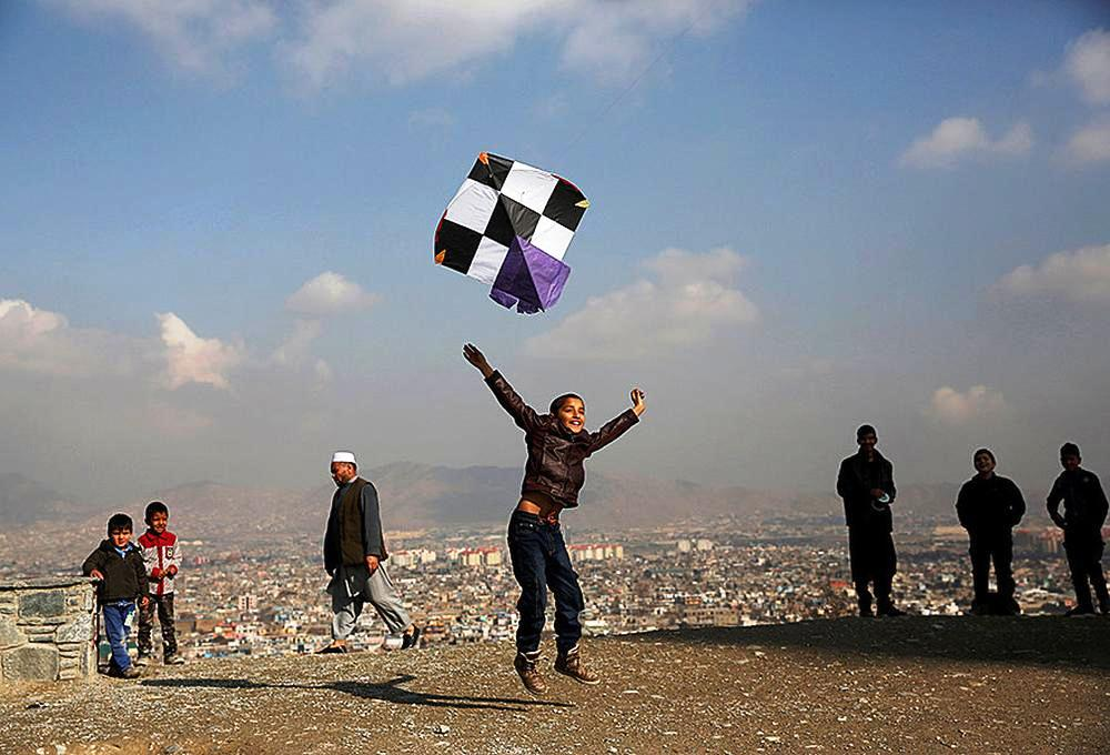 An Afghan boy launches a kite as he plays on top of a hill in Kabul.