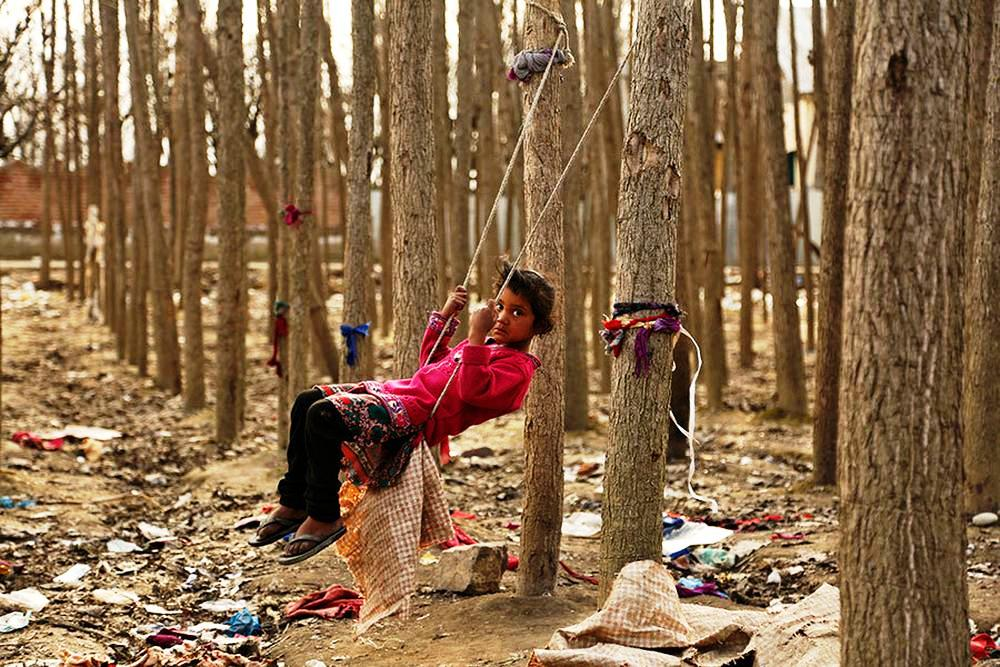 A child plays on a swing outside her riverside shanty home in Srinagar, Indian-controlled Kashmir.