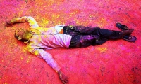 A Hindu devotee, smeared in coloured powder, takes a rest on a road during a procession for Holi celebrations in Kolkata.