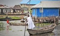 A priest from the Celestian Christian church moves to a pirogue. The Celestial Christian Church is a syncretistic  faith between Christianity and African religions founded in Porto Novo (Benin) in 1947.
