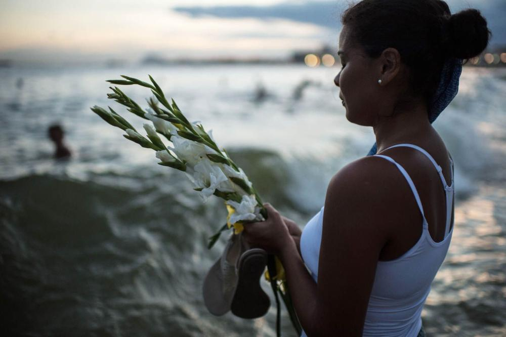 A young lady offers flowers as a tribute to Yemanja.