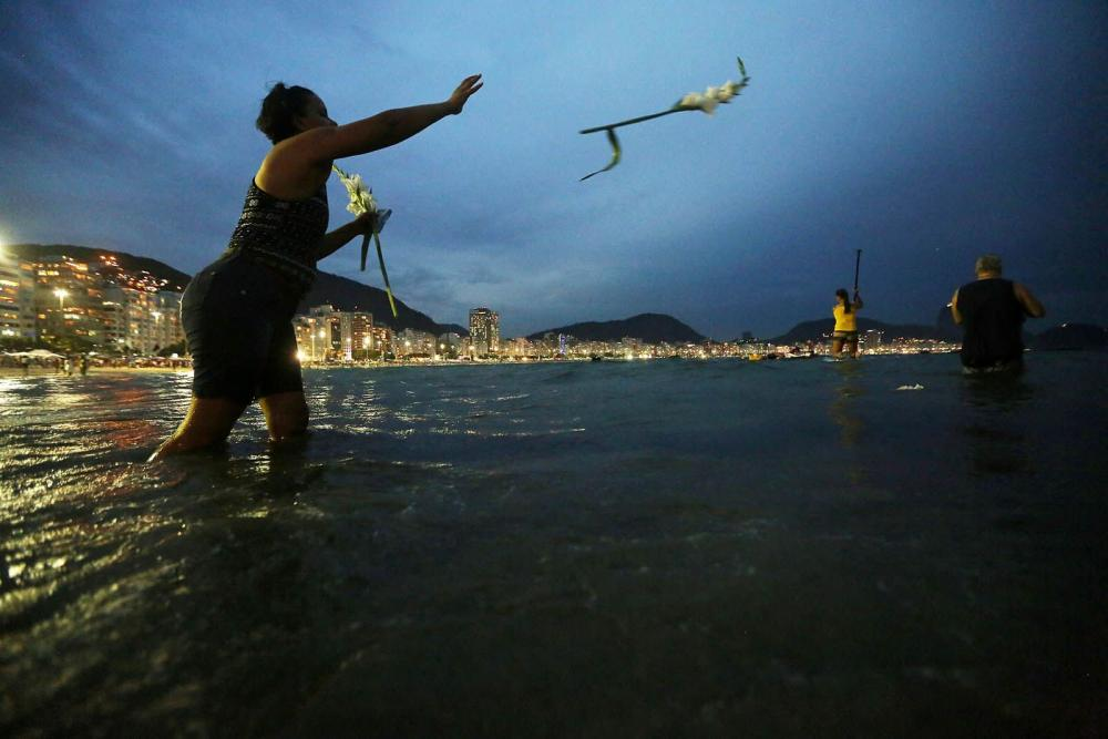 A worshiper tosses flowers into the ocean during a ceremony honoring Yemanj.