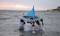 Faithful carry a boat out to sea, filled with offerings to Yemanja.