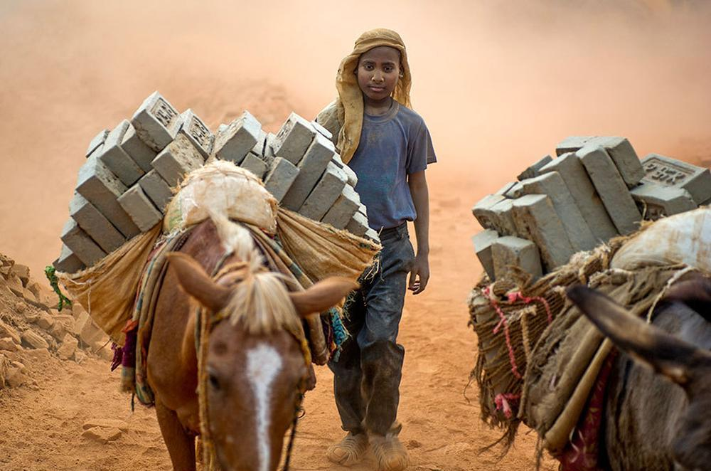 Children load and unload finished and unfinished bricks at a brick kiln in Dhadang, Nepal.