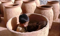 An Afghan boy smoothes the inside of a clay oven at a pottery in Kabul. There are 246 million children workers around the world.