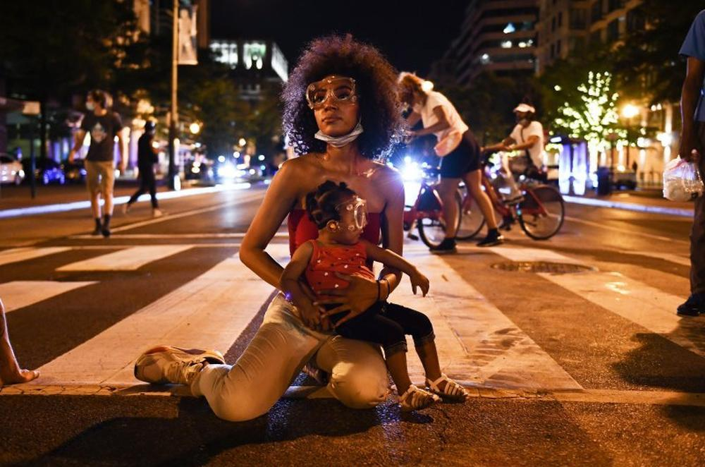 Demonstrator Twana Buck and her daughter Bonita sit in the street near the White House as protests triggered by the death of George Floyd while in police custody.