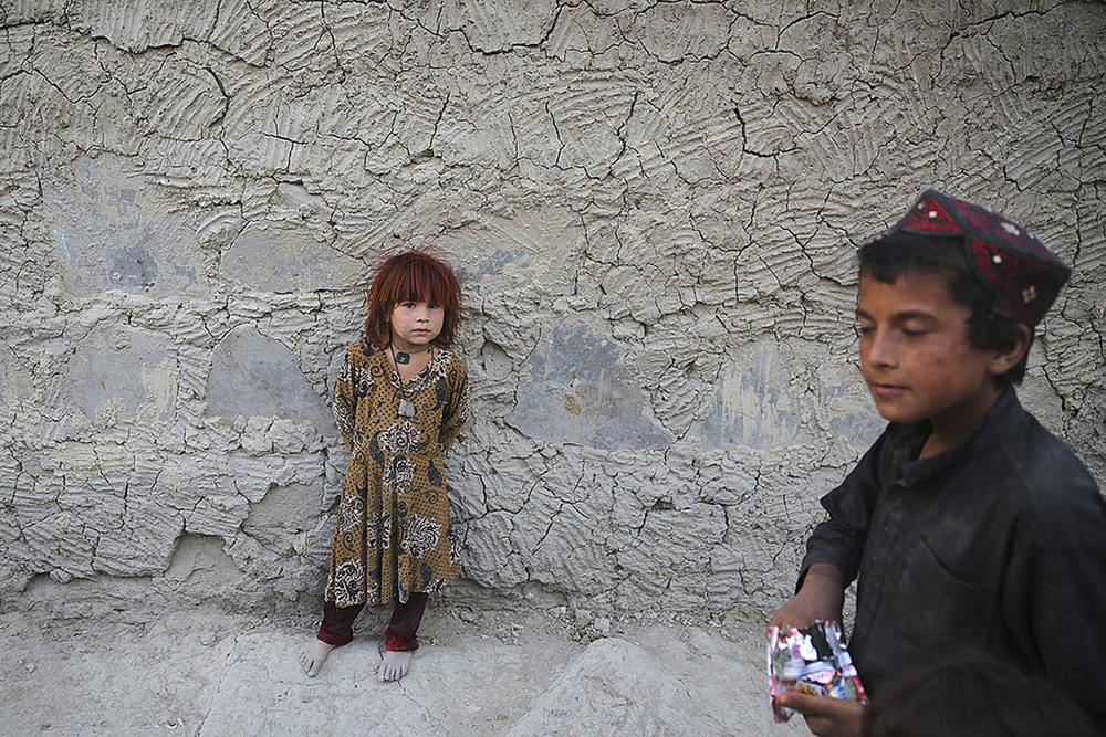 Afghanistan. An internally displaced Afghan girls stands outside her house at a camp in Kabul.