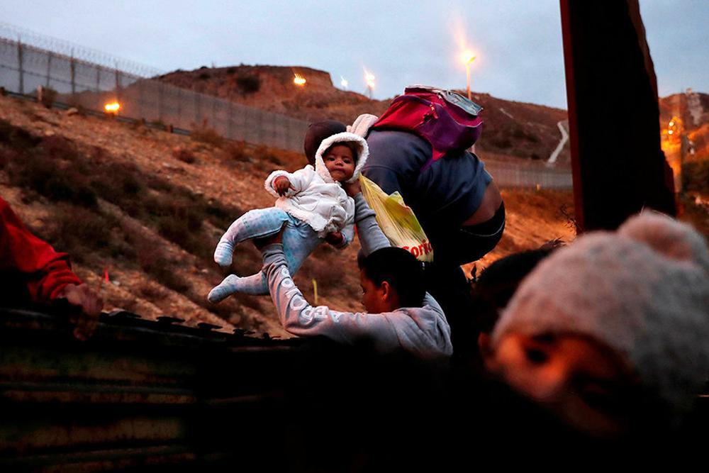 Honduran migrants, jump over a border fence into the US from Tijuana, Mexico.