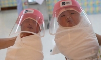 Nurses hold new-born babies wearing protective face shields at the Praram 9 Hospital in Bangkok, Thailand.