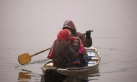 A women covers her baby with a stole as they travel in a boat on Dal Lake during a snowfall in Srinagar, Indian-Administered Kashmir.