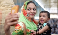 Pakistan. A mother with a child takes a selfie.