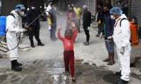 A young girl is sprayed with disinfectants in Kathmandu, Nepal.