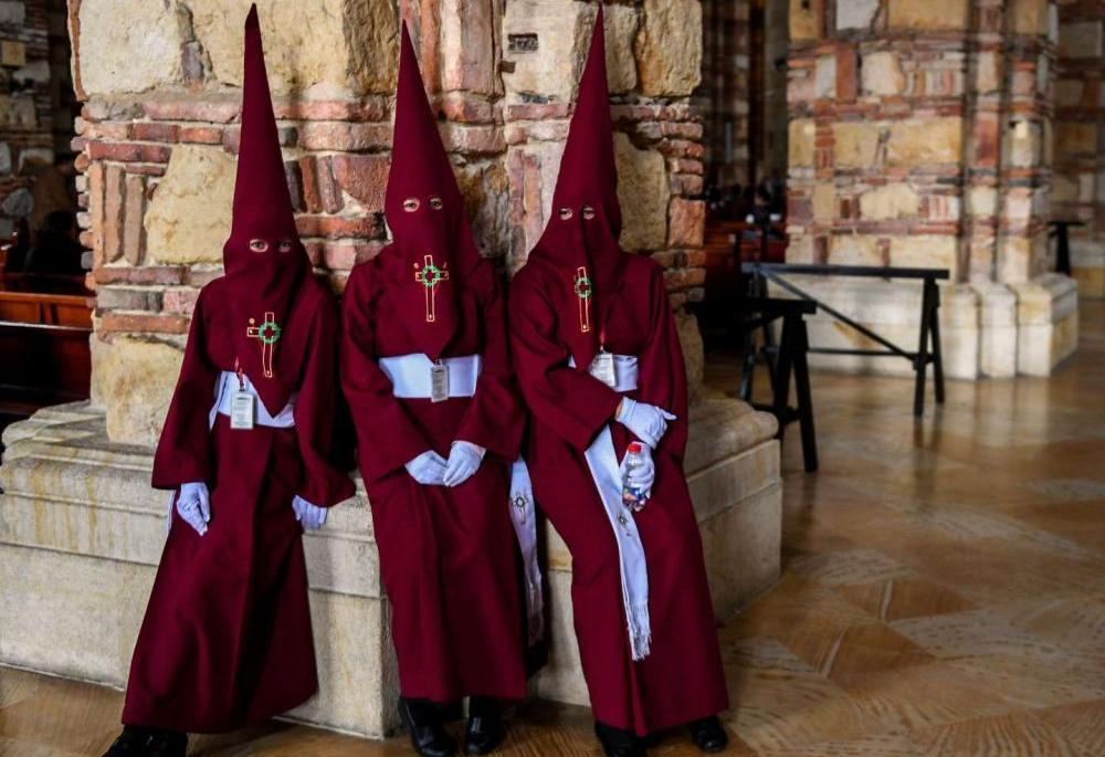 Colombia. Members of Nazarenos brotherhood take a rest after participating in the Way of the Cross in Zipaquira.