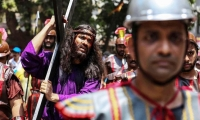 Mumbai. India. A penitent dressed as Jesus Christ takes part in a procession.