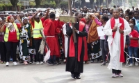 Kenya. A priest leads hundreds of followers as he carries a cross through the streets.