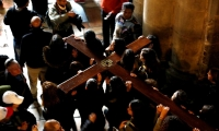 Jerusalem. Worshipers carry a wooden cross into the Church of the Holy Sepulchre.