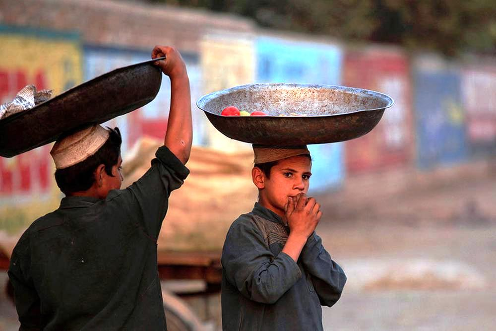 Boys wait to collect food from a pile of rotten vegetables near a dustbin in Peshawar.