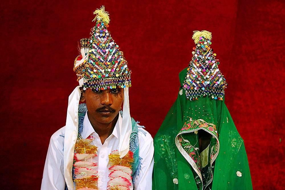 A bride and groom wearing traditional handmade garlands wait for their wedding to start during a mass marriage ceremony.