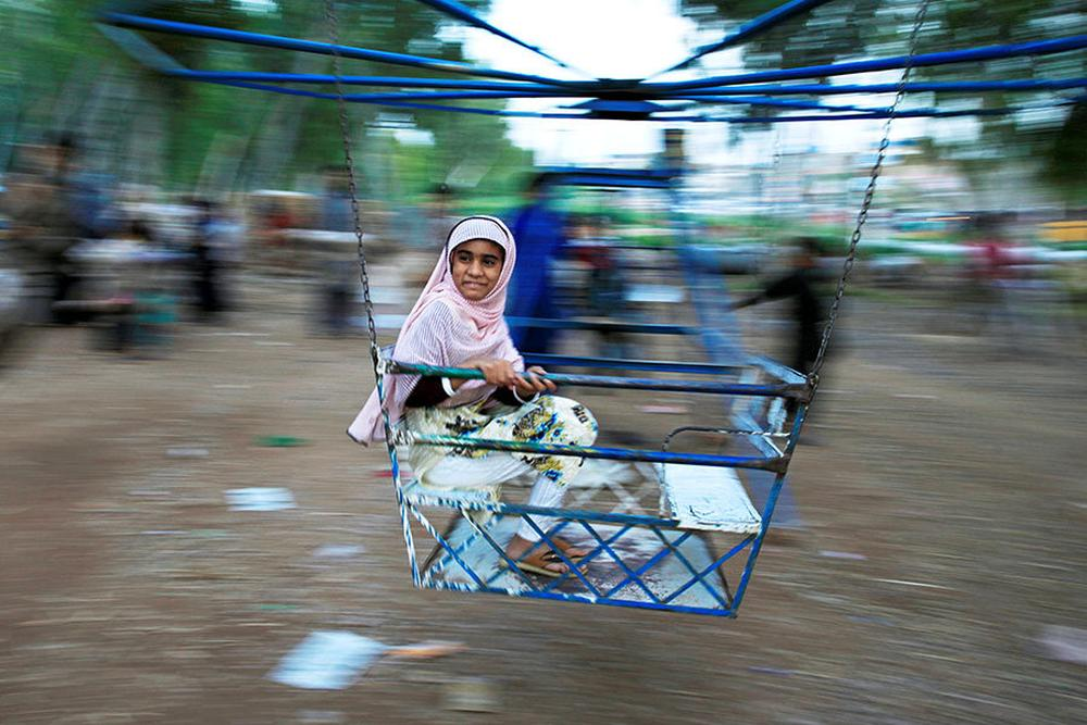 A girl rides a swing along a roadside in Rawalpindi.